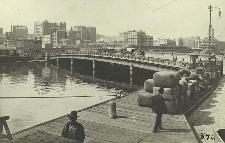 QUEENS BRIDGE & MELBOURNE'S CBD c.1910 A view of Melbourne's CBD and Queens Bridge from the south side of the Yarra River. The earlier image was taken from Princes Wharf. one of a number of wharves that were located on both sides of the river. From the 1850s, the south bank river frontage was opened up for shipping and other related uses. By 1860 the river wharves could cater for 36 vessels.
