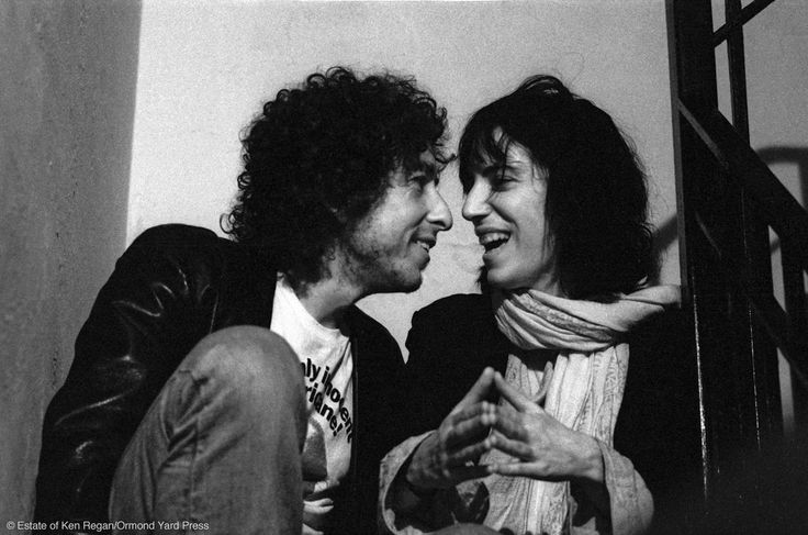Bob Dylan & Patti Smith Party in Greenwich Village where Ken Regan takes a famous series of photographs of Patti Smith and Bob Dylan in animated discussion on the stairs.  Patti Smith was invited on tour, but didn't go. Smith recalls Phil Ochs pouring a bucket of beer over her at this party, echoing an earlier incident where singer Bette Midler throws beer in her face.  CREDIT: © Estate of Ken Regan