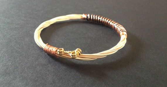 This is a handmade Bronze coloured Recycled guitar string bracelet bound with some Bronze wire. The bracelet is stackable. Very unique, suitable for men, women, teenagers.  Wear a piece of Manchesters rich music heritage with our recycled guitar string Bangles. We source all our strings from Manchesters leading music store which is frequently used by famous musicians on the manchester music scene. Who knows who would have used the strings we make our products with. All our bangles are…