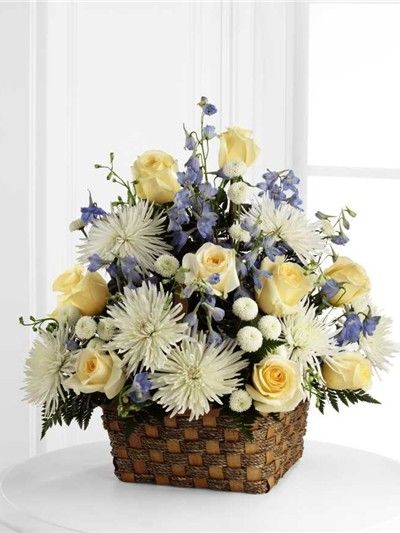 Blue, yellow and white funeral flowers for a child in a natural basket