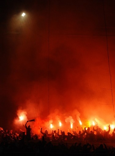 Galatasaray's supporters light flares during the UEFA Champions League quarter-final first leg football match Real Madrid vs Galatasaray on April 3, 2013 at Santiago Bernabeu stadium in Madrid. AFP PHOTO/ DANI POZO
