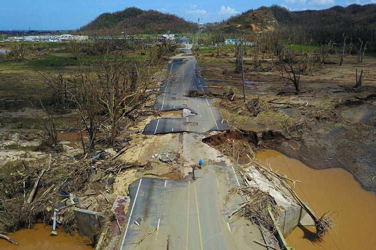 After the passage of Hurricane Maria, a man rides his bicycle through a storm-damaged road in Toa Alta, west of San Juan, Puerto Rico.