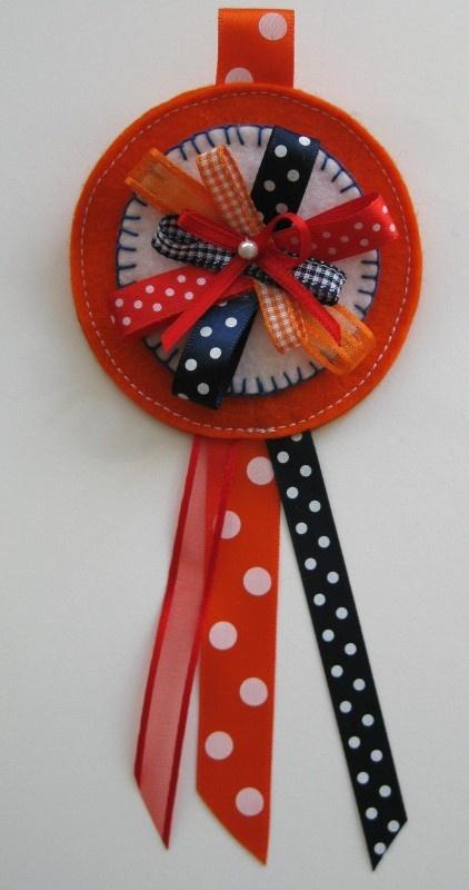 Prinsessen broche oranje met lintjes en pareltje