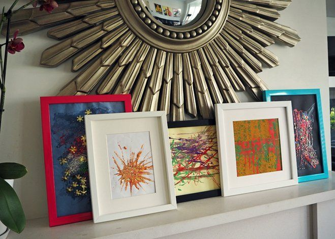 children's art displayed in five multicoloured frames on a floating shelf under a starburst mirror