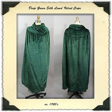 This is such a lovely deep green velvet opera cape from the 1920's. It has seamed shoulders and the velvet is gathered into the front and back yoke seam. The silk lining has the most beautiful striped print of solid green and tree with a geometric border print with little daisies.