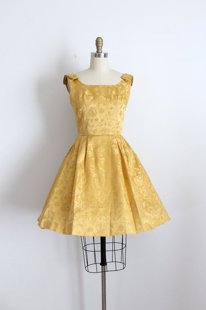 Beautiful gold brocade party dress from the early 1960s. This dress features a fitted bodice and waistline with an open skirt, and cute bow like