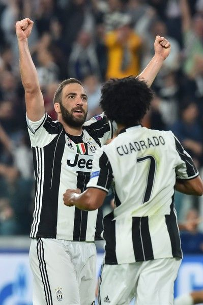 Juventus' forward from Argentina Gonzalo Higuain (L) and Juventus' forward from Colombia Juan Cuadrado celebrate a gaol by teammate Juventus' forward from Argentina Paulo Dybala during the UEFA Champions League quarter final first leg football match Juventus vs Barcelona, on April 11, 2017 at the Juventus stadium in Turin.  / AFP PHOTO / GIUSEPPE CACACE