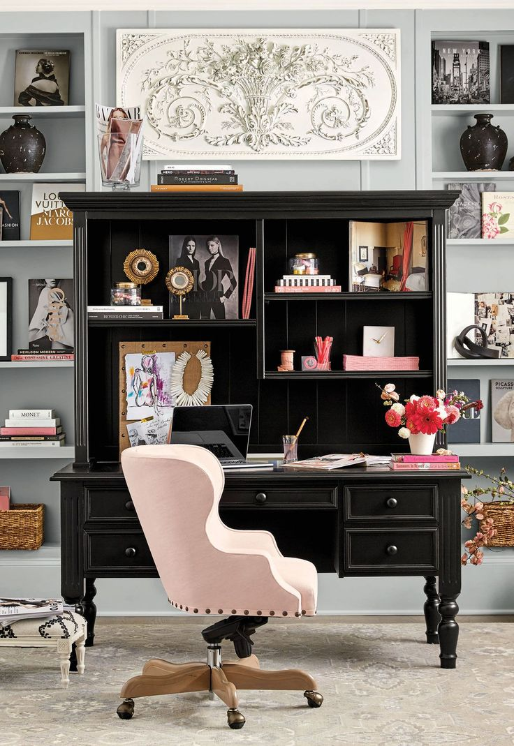 A blush pink desk chair and accessories add a feminine touch to a black secretary desk.