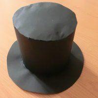 maak om een rol w.c.papier deze hoge hoed. Tekst erbij: In mijn hoed draag ik reserve mee. hang mij daarom op de w.c. Of: In mijn hoed draag ik reserve mee, neem mij daarom op reis mee (Leg hem in dit geval op de hoedenplank van de auto)