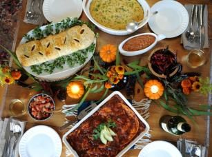 "An unconventional plant-based Thanksgiving spread, including, clockwise from top, sweet potato casserole, Mexican lasagna, and baked ""turkey."""