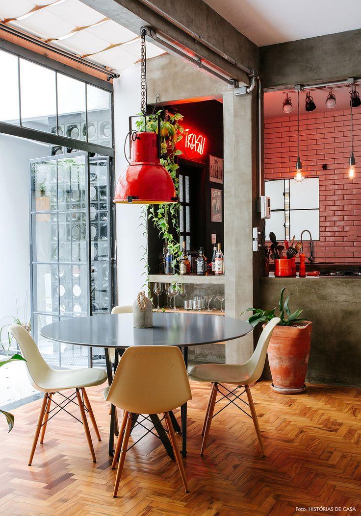 Sala de jantar tem mesa redonda, cadeiras Eames e pendente industrial.