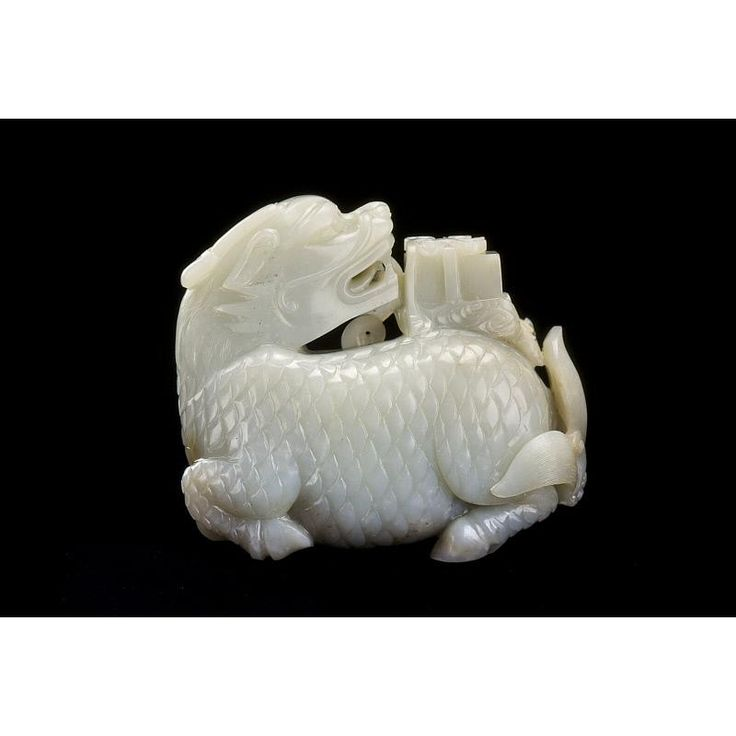 A Qilin offering a book  Date: 1644-1912 (Qing). Location: China.  A jade carving of a   mythical creature known as a qilin. Other names include kylin, chilin, and simply a unicorn. The creature has a body of a deer, head of a wolf, the tail of an ox, and hooves of a horse. This particular object shows a book on the creature's back, believed to be spat from its mouth.   It was given as gift to children of wealthy families to bring good luck, and hope for the child to become a scholar.