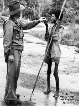 Balikpapan, Borneo. 1945-07-18. Many cases of malnutrition were among the natives of Samboja, thirty eight miles from Balikpapan, when Australian troops captured the town. Here a war correspondent hands food to one of the sufferers from the Japanese occupation.