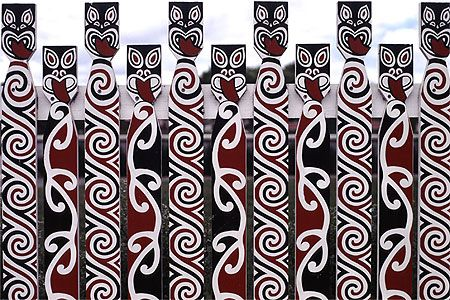A fence in Rotorua, New Zealand decorated with Maori art.
