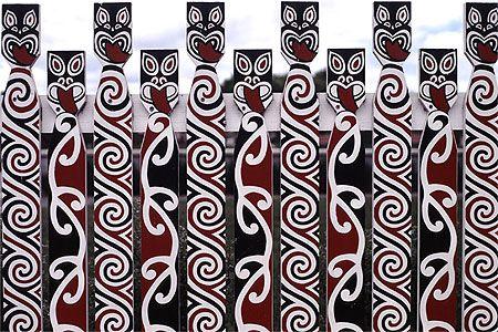 A fence in Rotorua, New Zealand decorated with Maori art.