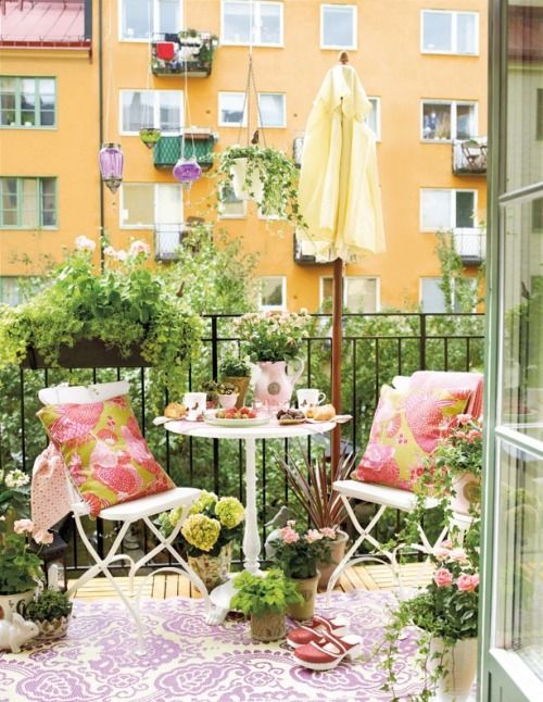 I like the pink patio cushions against the green of the balcony garden