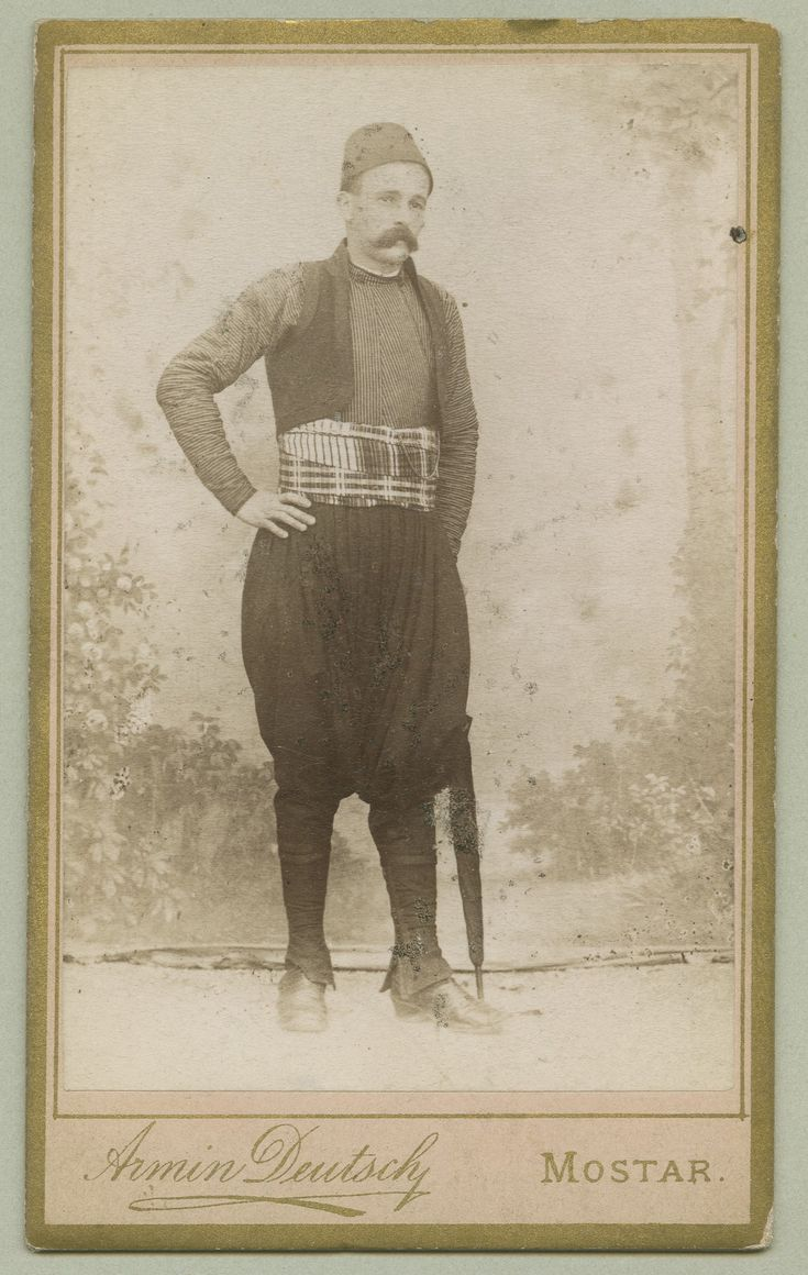 Studio portrait of a man in urban clothes, © The Austrian Museum of Folk Life and Folk Art. 1879-1918 Full-length shot of a man wearing a typical Muslim town costume: close-fitting trousers with a low, baggy crotch (čakšire), a short vest (jelek) with a jacket (džamadan) underneath, a flat cap and gaiters. He is holding a cigarette in his left hand. There are weapons attached to his belt. He is also wearing a medal.