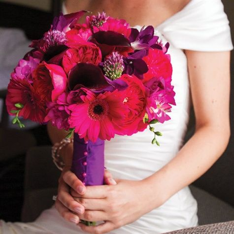 The bridal bouquet was a bright mix of gerbera daisies, roses, freesia, calla lilies, dendrobium orchids and mini allium, all in vibrant shades of pink and purple. For a finishing touch, the stems were wrapped in purple silk dupioni ribbon and fastened with hot-pink pins.