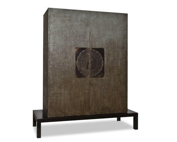 PREITE Armadio imponente di forma essenziale, valorizzata da un rivestimento di yuta trattata con una laccatura di colore grigio-bruno. Il basamento è lineare ed elegante, in lacca nero ebano. L'importante maniglia gioiello è una fusione in bronzo ricavata da un pizzo antico del nord Italia. Il mobile è rifinito anche sul retro e sul tetto. L'interno è in legno tinto con anilina grigia.  Dimensioni: Mobile: H150xP50xL120 cm Tavolino di sostegno: H20xP60xL150 cm Maniglia: 40×40 cm