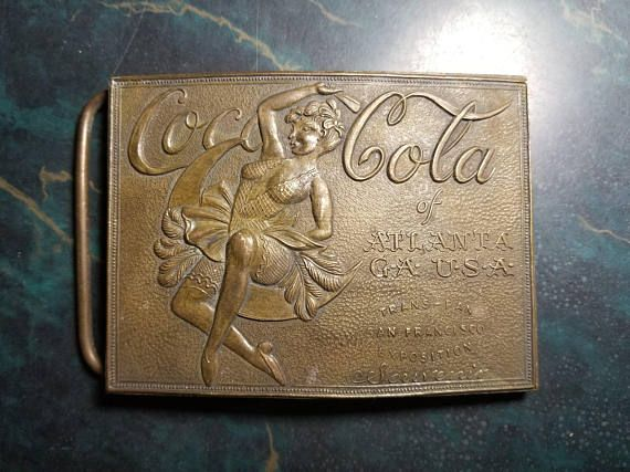 For sale is a vintage solid brass Coca Cola fantasy belt buckle. This is an item that was made by Coca Cola as a souvenir for an event that never happened, specifically the 1915 Trans-Pan San Francisco Exposition. The front of the belt buckle reads Coca Cola of Atlanta GA USA,