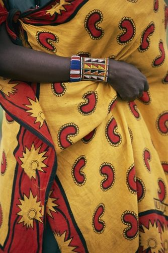 Africa.  A woman holds onto her traditional costume wrapped around her.  Kenya | ©Bruce Dale / National Geographic