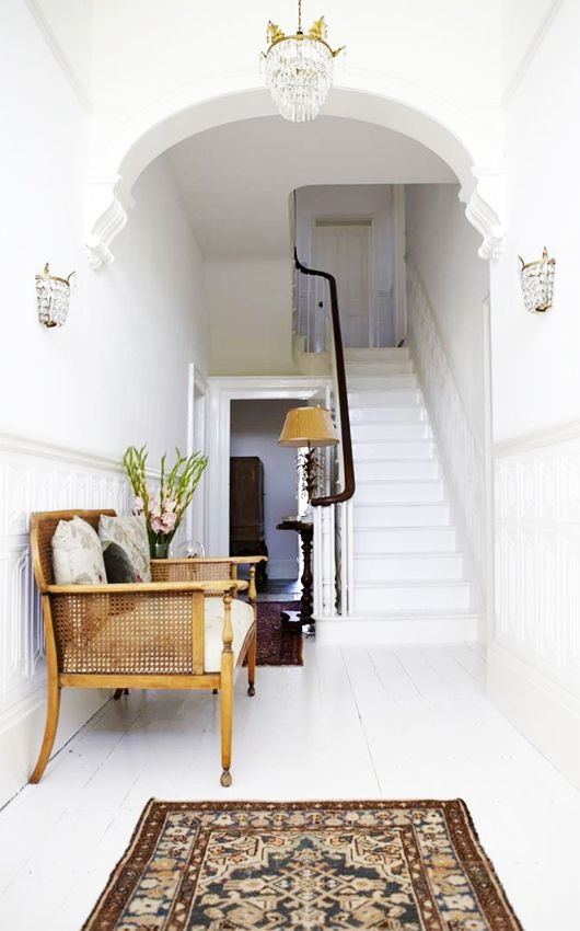 White entry with beautiful archway | antique cane settee | antique crystal bead lighting