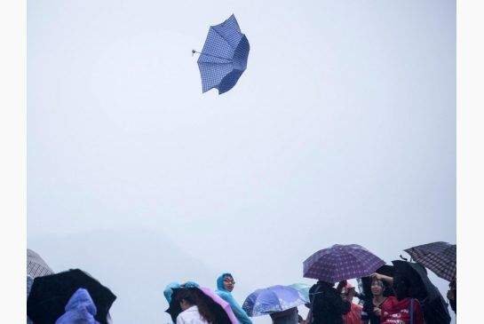 An umbrella blows away in strong winds at West Lake in Hangzhou in eastern China's Zhejiang province Saturday, July 11, 2015.