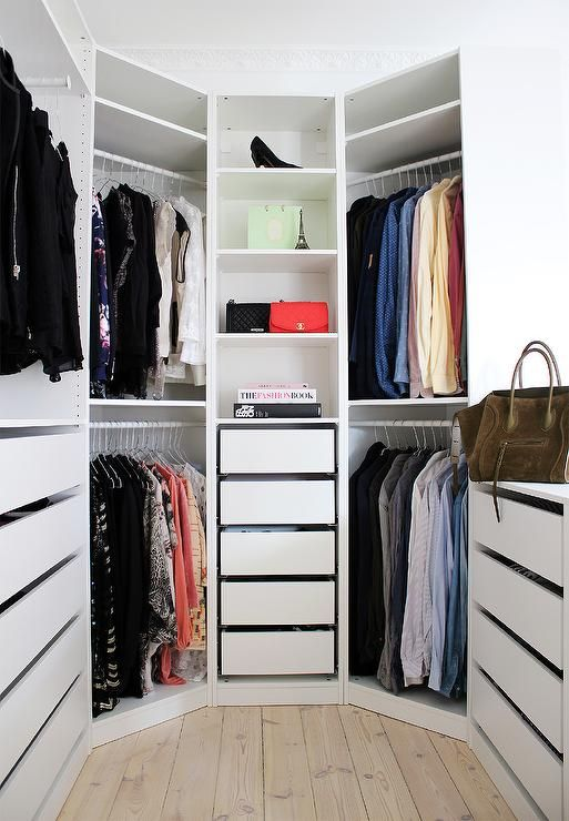 Chic closet is filled with an Ikea Pax System boasting modular shelves and pull out drawers including a closet peninsula.