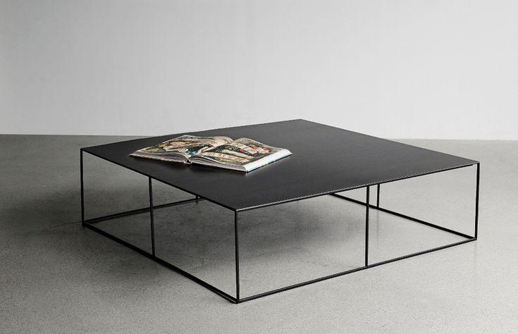 Modernt och snyggt soffbord i svart metall. Luftigt underrede av metallstänger och en stor skriva ovanpå.