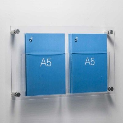 Easy to install perspex A5 brochure holder. Fixed to the wall with anodised aluminium stand offs. This model has two A5 pockets and is 42cm wide. Supplied with wall fixings, screws and wall plugs. All you have to do is drill 4 holes.