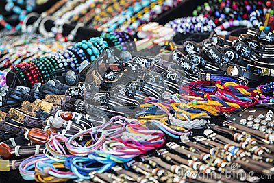 Detail view of many various colorful leather bracelets with zodiacal signs, beads, accessories and souvenirs.