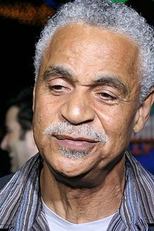 "Ronald Earle ""Ron"" Glass (July 10, 1945 – November 25, 2016) was an American actor. He was known for his roles as the literary Det. Ron Harris in the television sitcom Barney Miller (1975–1982), and as the spiritual Shepherd Derrial Book in the short-lived 2002 science fiction series Firefly and its sequel film Serenity."