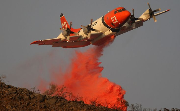 A firefighting airtanker drops Phos-Check fire retardant just before sunset in one of its final drops of the day to try to control the eastern flank of Tea Fire before the winds might return on November 14, 2008 in Montecito, California. Thirteen people were injured and more than 100 homes destroyed in the first few hours as evening Sundowner Winds reached 70 mph, pushing the wildfire into multi-million dollar ocean-view homes the night before.