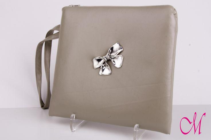 Bolso de mano en napa beige con cierre de cremallera y agarre lateral y decorado con lazo metálico. www.monetatelier.com