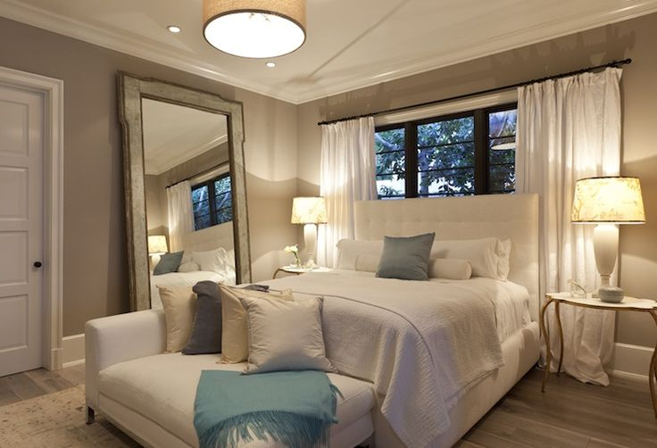 Chic, cozy bedroom with bed in front of window covered in white cotton drapes. White tufted headboard installed in front of window paired with soft white bedding and slate blue pillow flanked by brass clover tables with tall white lamps. Master bedroom features warm gray walls, antiqued mirror floor mirror, white chaise lounge filled with turquoise throw blanket at foot of bed over wood floors.