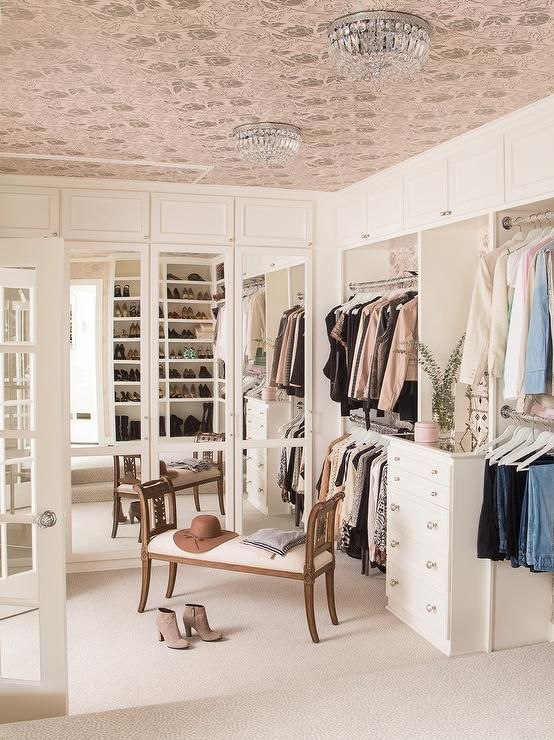 Exquisite walk-in closet features a pink wallpapered ceiling dotted with crystal beaded flush mount lights illuminating floor to ceiling built-ins boasting mirrored closets, stacked clothes rails and a built-in lingerie dresser alongside a bench.