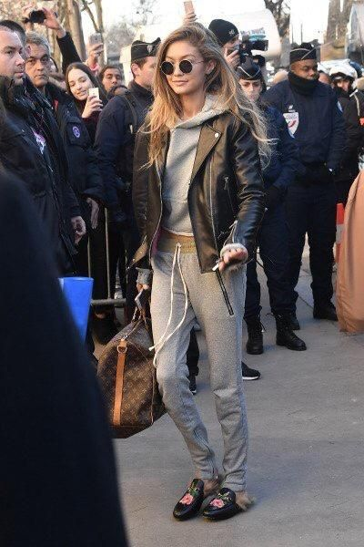 Gigi Hadid wearing Oliver Peoples The Row After Midnight Sunglasses, Gucci Princetown Fur Lined Mules, Louis Vuitton Keepall 55 Bandouliere Monogram Bag, Fear of God Drawstring Pants, Amiri Shotgun Cropped Hoodie in Grey and Nour Hammour Leather Jacket