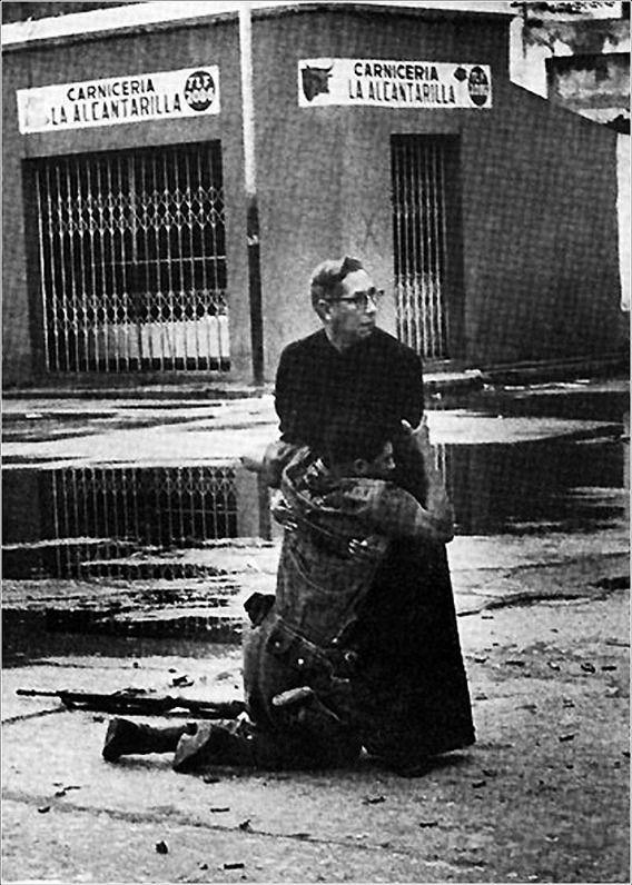 """""""海軍牧師ルイスPadilloは、ベネズエラの反乱の間に狙撃火災で負傷した兵士に最後の「救い」の儀式を路上でささげる。"""""""