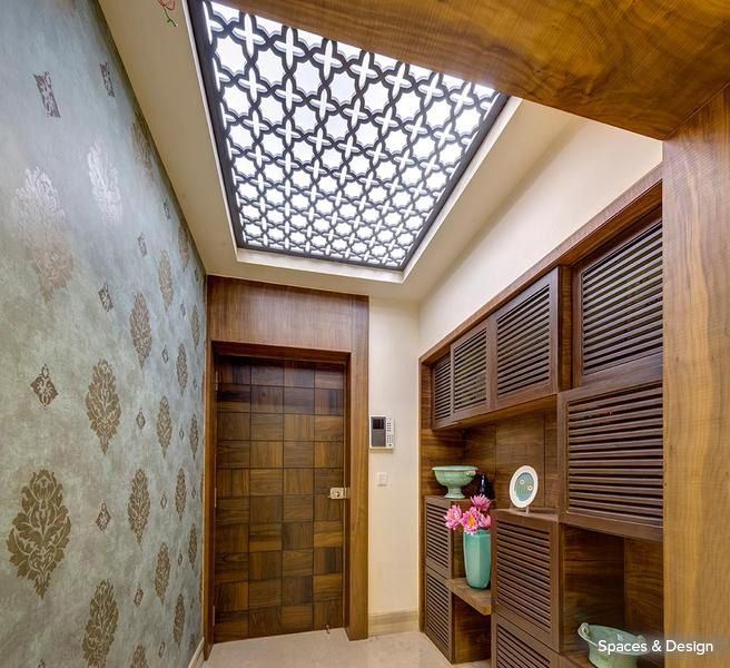 An artistic wooden ceiling allowing natural white light to seep through, beautifully invigorating this foyer #homedecor #designs #ceiling #foyer Design Courtesy - Spaces & Design, Kolkata