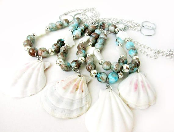 A set of seashell curtain tiebacks which will add the beach vibe to any room in your home. A beautiful set of drapery holdbacks that featured a real natural sea shell center. These tiebacks for curtains have ocean colored beads and a shell star on each strand. Ocean colors to match