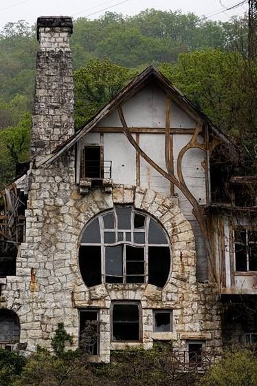 Unique stone-rimmed statement window beside stone chimney. Lovely cottage with organic lines.