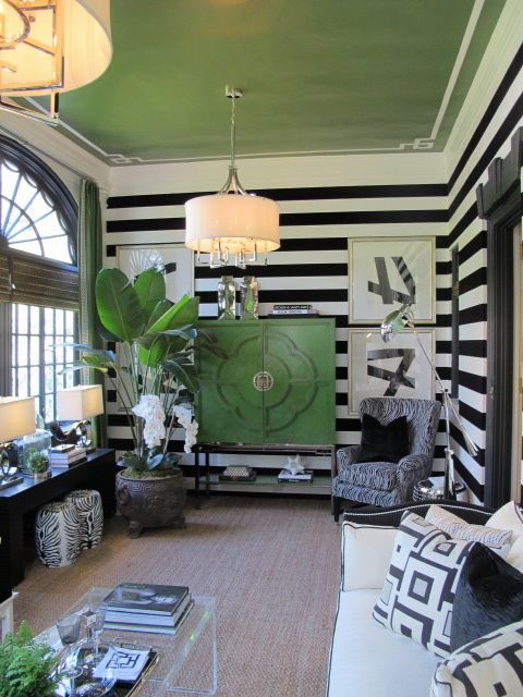 """""""If you're not going to be bold, why be anything"""" may have been the mantra of the Lillian August interior design team of Richard Cerrone and Angela Camarda, who put together the black, white and green sunroom in the Showhouse of Westchester. Broad horizontal stripes, a green-painted ceiling, black-and-white furnishings and green curtains gave the air of Regency chic with a twist."""