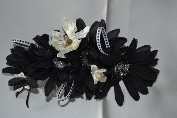 Black daisies with silver centres interspersed with small white magnolias. Accented with black and white ribbon. Perfect for a black and white