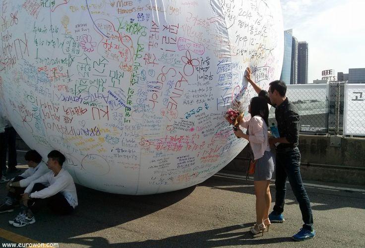 Pareja coreana escribiendo mensajes en una gran pelota blanca.