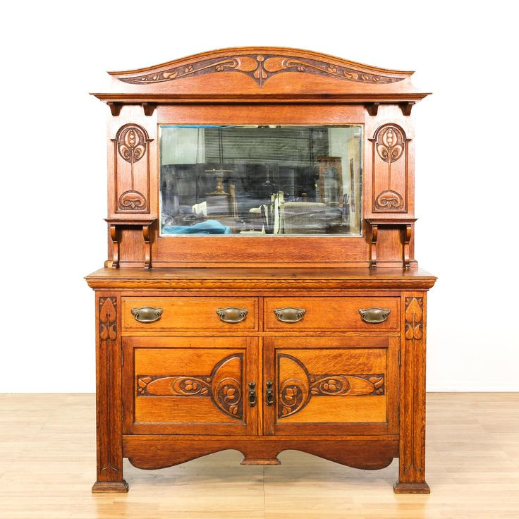 This arts and crafts sideboard buffet is featured in a solid wood with a gorgeous cherry oak finish. This craftsman credenza bar has a large curved mirror top with 3 drawers, large interior cabinets and carved floral accents. Stunning storage piece perfect for a dining room! #americantraditional #storage #buffet #sandiegovintage #vintagefurniture