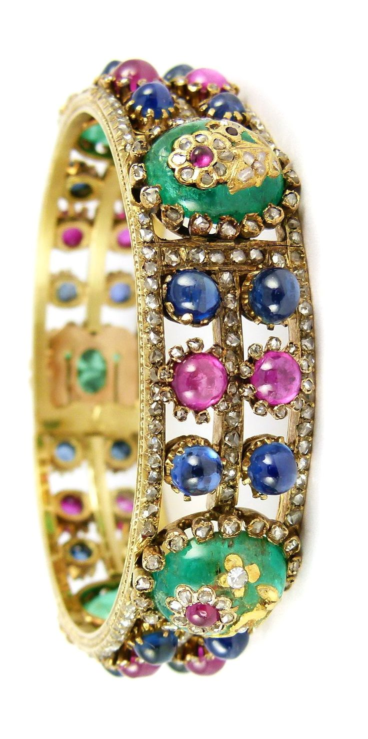 19th century cabochon emerald, sapphire, ruby and diamond bangle, French c.1890, the openwork rose diamond triple line frame set with pairs of round cabochon rubies and sapphires, all spaced by oval cabochon emeralds, each inlaid with a diamond and ruby set flower stem, mounted in gold, serial number 4370