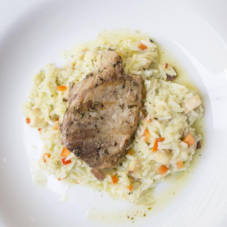 Escalopa de lomo de cerdo sobre un arroz cremoso en una mantequilla de hierbas