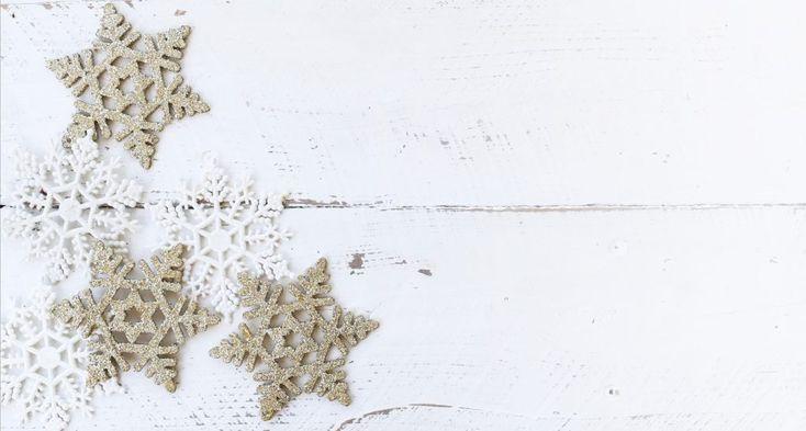 Déco en flocons de neige découpés en blanc et beige sur une planche en bois peinte en blanc.