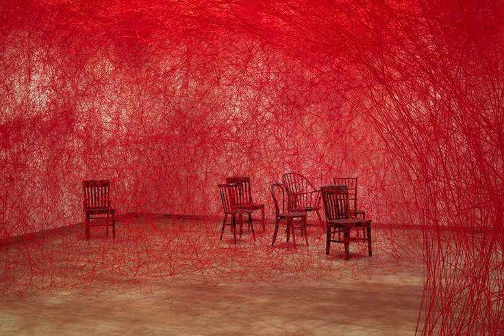 Chiharu Shiota tesse a mano un grande bozzolo di filo rosso e sedie antiche L'artista giapponese Chiharu Shiota ha tessuto a mano un'enorme installazione di fili rossi, che in parte collegavano e in parte nascondevano alla vista, delle sedie d'epoca. L'opera che ricorda un g #arte #installazione #colore