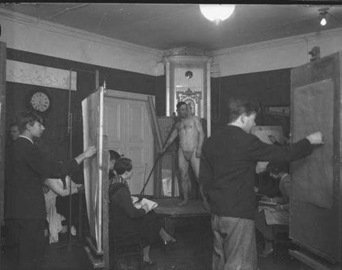 Melkein alaston mies seisoo kaakeliuunin edessä mallina keppiin nojaten ja Turun piirustuskoulun opiskelijat piirtävät mallia erikokoisille papereille. Piirustuskoulu toimi 1933 - 1936 asuinhuoneistossa, johon kuului viisi huonetta ja keittiö puutalossa osoitteessa Uudenmaankatu 14. Tilat olivat hyvin ahtaat ja oppilaiden täytyi työskennellä vieri vieressä. Kuvaaja: Turun sanomat.  TS4926: